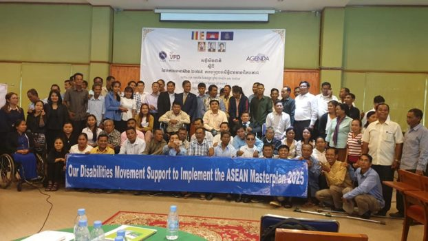 "Participants of the conference is holding a long banner with ""Our Disabilities Movement Support to Implement the ASEAN Masterplan 2025"" written on it."